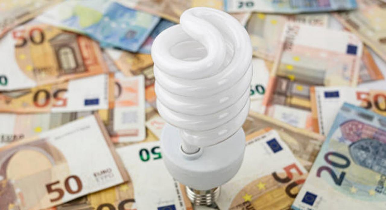 Bizkaia reduce el IVA de la electricidad y suspende el IVPEE para abaratar la factura de la luz. Imagen de una bombilla sobre dinero en metálico