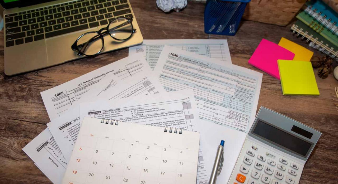 COVID-19: Bizkaia modifica su reglamento de recaudación. Imagen de formularios de impresos para impuestos y unas gafas sobre mesa de trabajo