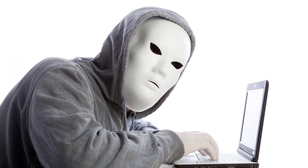 Hombre hacker con máscara y guantes usando un portátil. Falciani