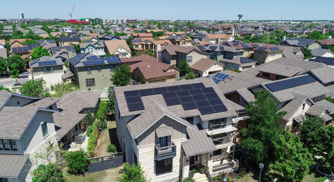 Tributación en el Impuesto sobre la Electricidad y en el Impuesto sobre el Valor de la producción de Energía Eléctrica del autoconsumo colectivo con excedentes sin compensación. Imagen de una zona residencial con placas solares en sus tejados
