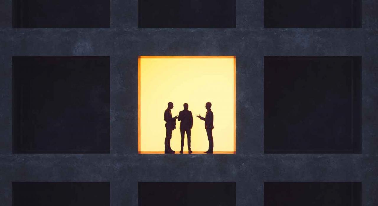 Imagen de un edificio de oficinas, una de ellas con la luz encendida donde se ve la silueta de tres personas hablando sobre el acuerdo de despedido