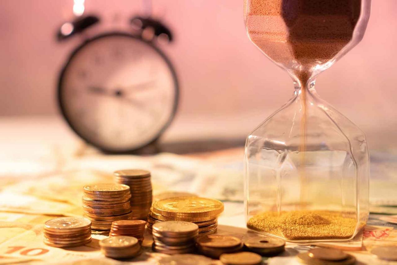 Aplazamiento de pago de deuda pública. Imagen de unas monedas y un reloj de arena