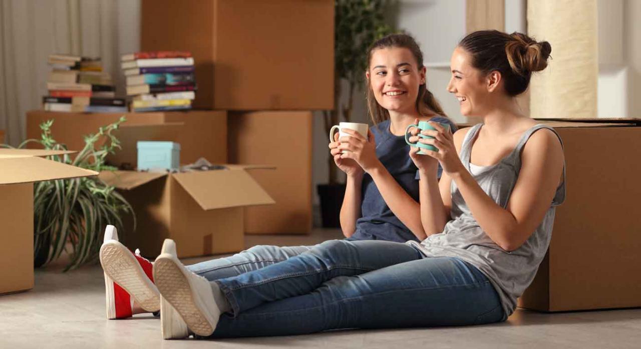 Deducción por arrendamiento en el IRPF. Dos jóvenes sentadas en el suelo con una taza en la mano y rodeada de cajas de mudanza