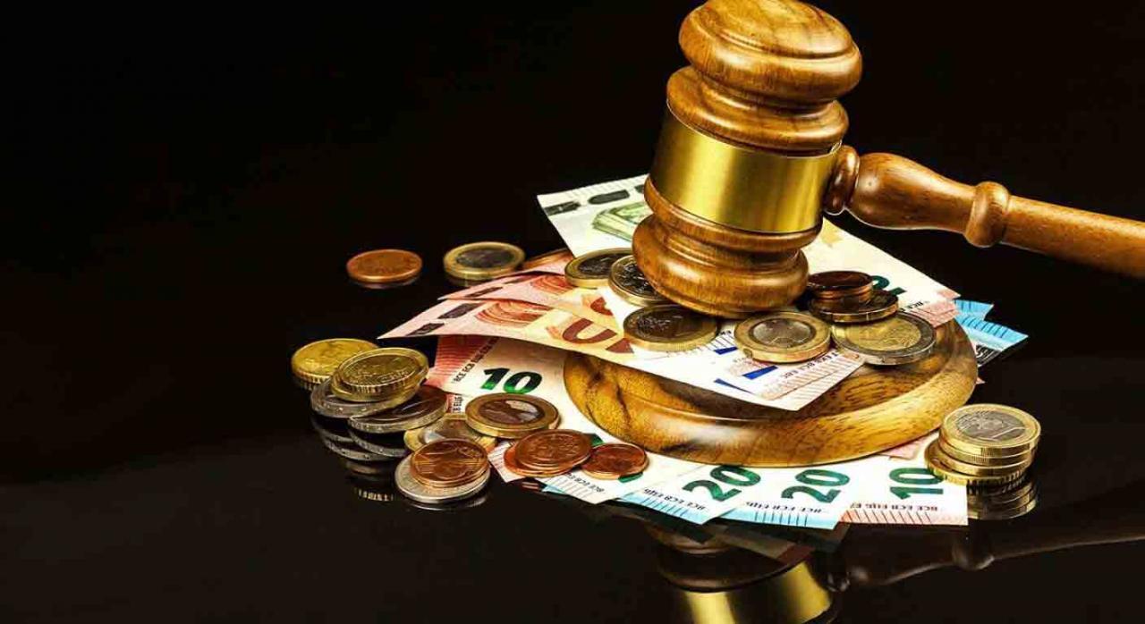 Autos y sentencias del Tribunal Supremo publicados durante la segunda quincena de junio 2021. Imagen de mazo de juez golpeando encima de un montón de billetes y monedas de euros