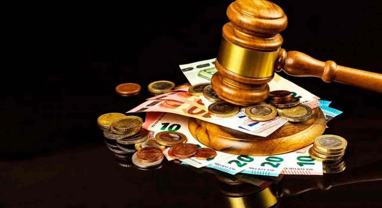 Ley fraude fiscal. Imagen de mazo de juez golpeando encima de un montón de billetes y monedas de euros