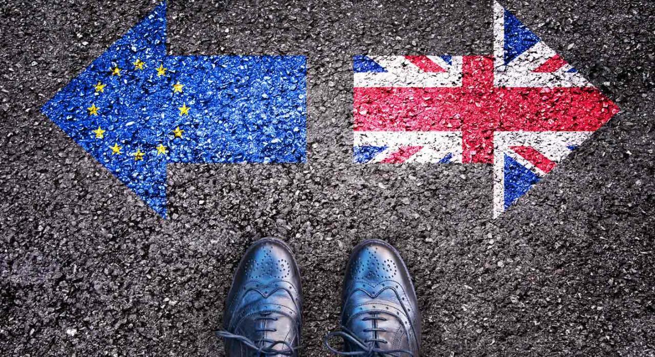 Brexit transición. Banderas con forma de flecha de la comunidad europea e inglesa dibujadas en el asfalto apuntando direcciones opuestas y unos zapatos de caballero en medio