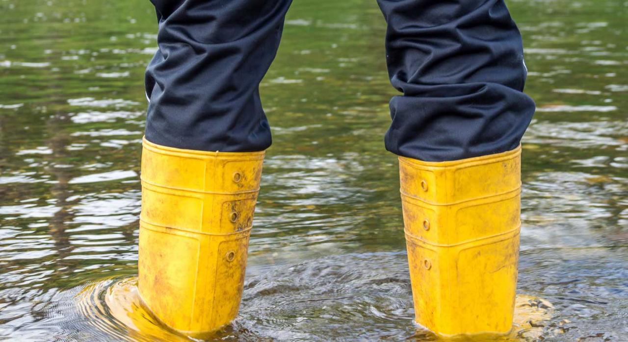 Persona con botas de agua en una inundación causada por temporal. Beneficios fiscales
