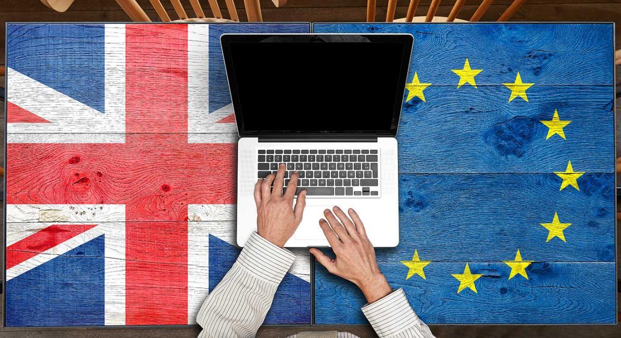 Brexit iva. Imagen de una mesa de madera con bandera europea y británica con portátil