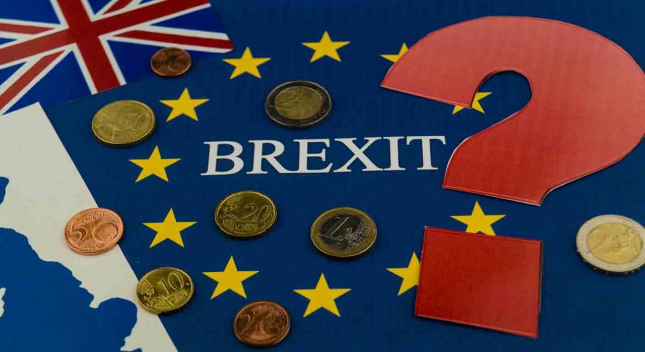 Devolución IVA Brexit. Palabra Brexit sobre la bandera del Reino Unido, la CEE, unas monedas y un signo de interrogación
