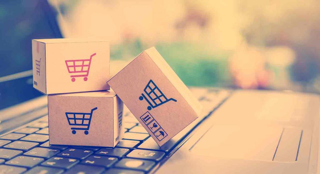 RIVA comercio electrónico. Tres cajas de cartón con el logo de un carrito, apiladas sobre un teclado