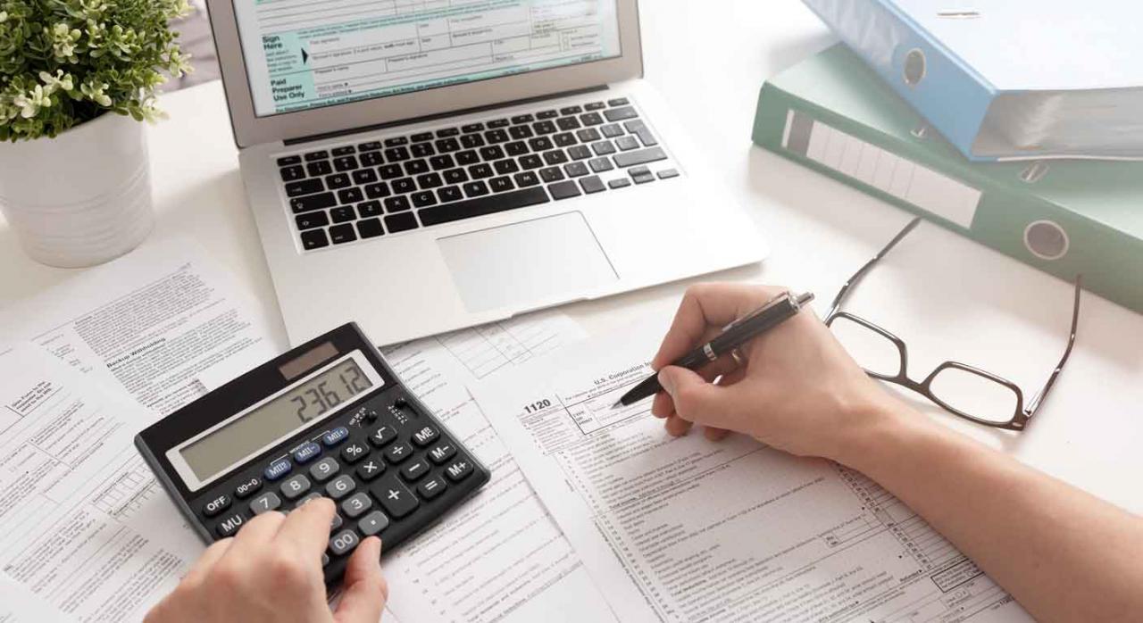 Impuesto sociedades 2020. Persona rellenando un impreso con una calculadora y un portátil