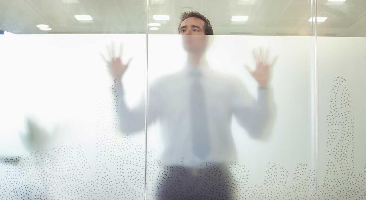 Cierre de oficinas de la AEAT. Imagen de un señor en la cristalera de una oficina
