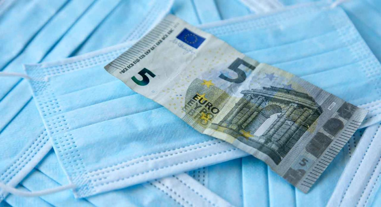 IVA mascarillas. Billete de cinco euros sobre un montón de mascarillas