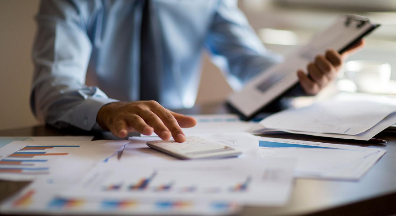 Claves aprovechar rentabilidad fiscal gestión patrimonios. Imagen de un hombre usando una calculadora