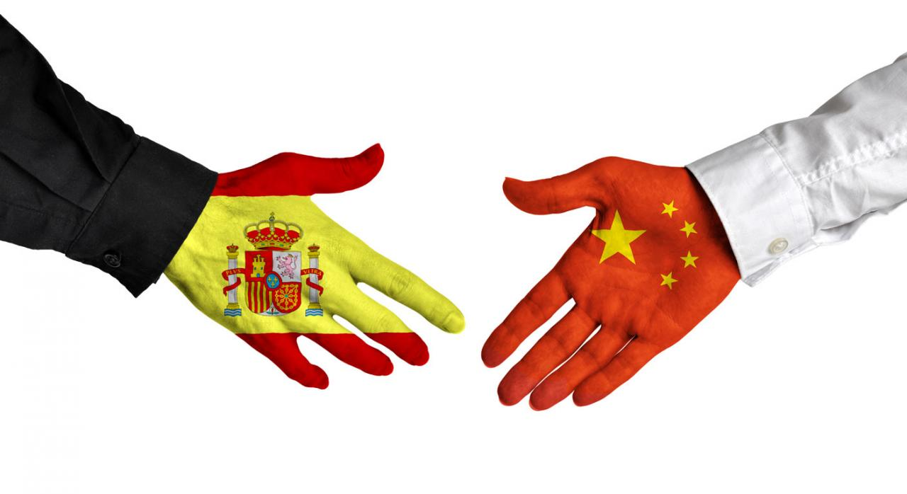 Convenio entre España y China. Dos personas estrechandose las manos pintadas con las banderas de España y China