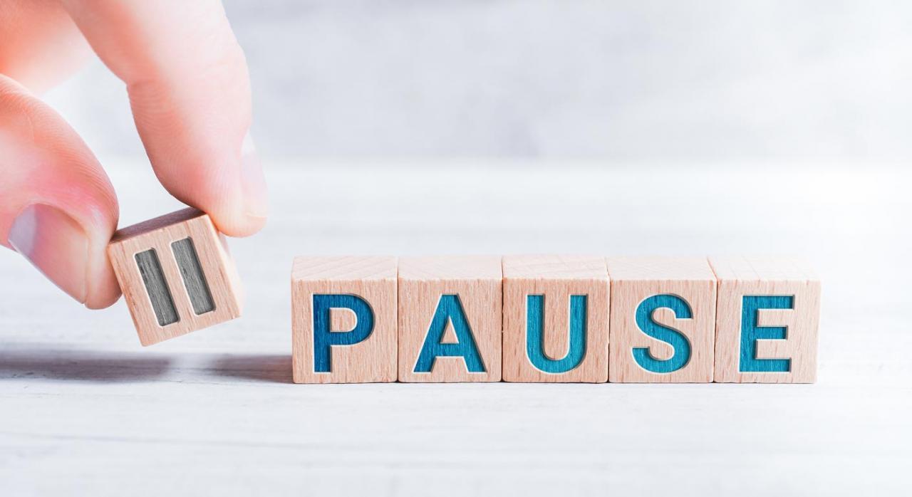 Medidas tributarias en Asturias con motivo del coronavirus. Imagen de la palabra pausa formada por bloques de madera con dedos masculinos en una mesa