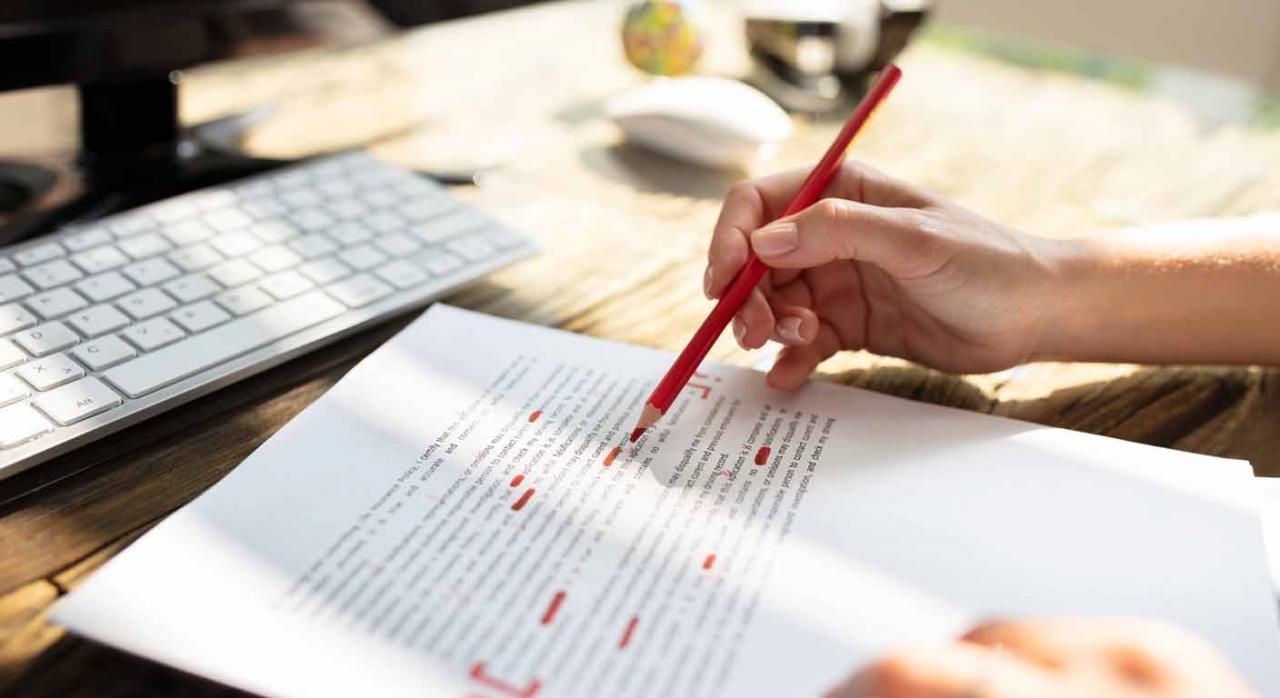 Correcciones en las deducciones de IRPF de Valencia. Persona corrigiendo el texto de un documento con un lápiz rojo