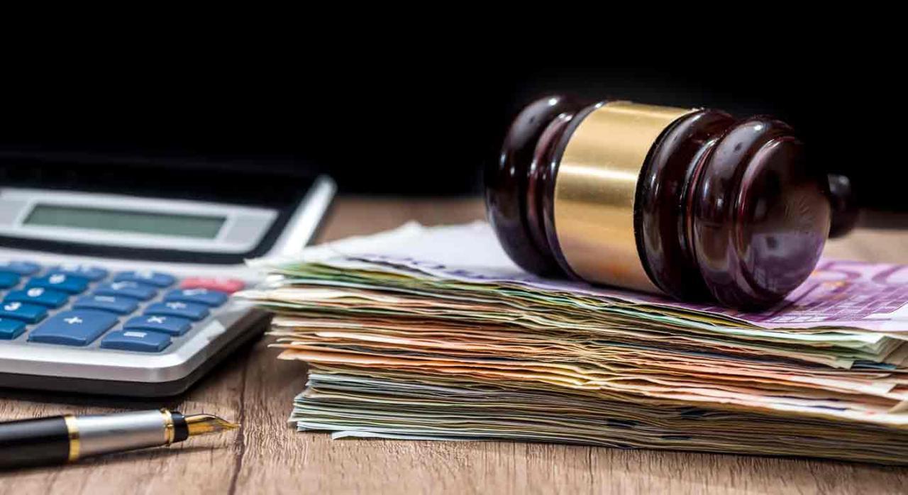 Costas judiciales. Una calculadora, una pluma y un mazo de juez sobre un fajo de billetes de euros