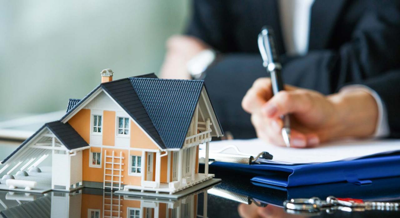 Cambios en la aplicación de la deducción por inversión en vivienda habitual. Imagen de una maqueta de casa unifamiliar sobre una mesa y una carpeta de contrato y una mano con un bolígrafo