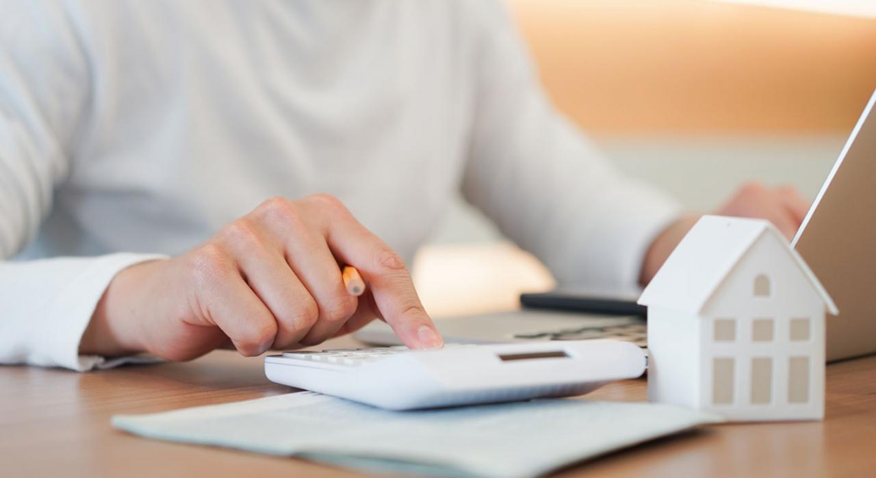 Deducción por adquisición de vivienda habitual. Persona con calculadora ordenador, calculando gastos hipotecarios