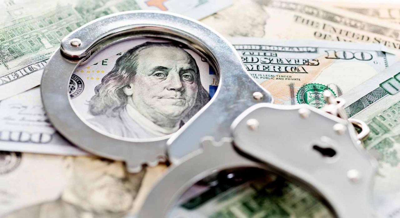 Se considera un préstamo simulado el dinero proveniente de un paraíso fiscal otorgado sin ningún tipo de garantías. Imagen de 100 dólares con unas esposas sobrepuestas