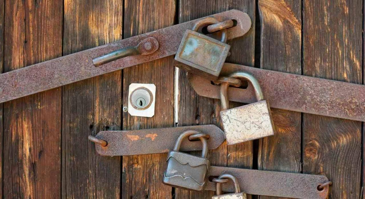 Entrada y registro de la AEAT en la sede social. Puerta de madera cerrada con varios candados