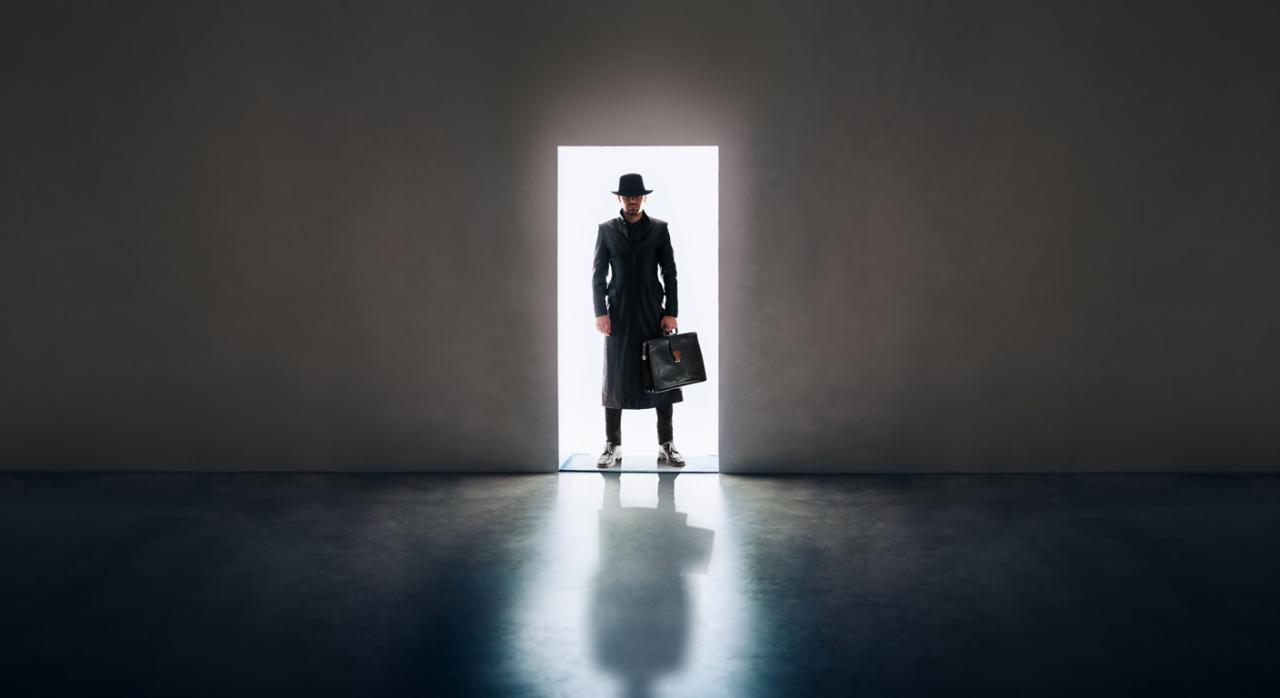 Inspección en sede empresa. Imagen de hombre con maletín entrado en un local oscuro