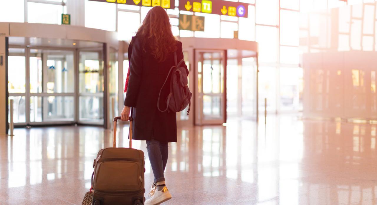Los rendimientos del trabajo correspondientes a los días de viaje al extranjero y de vuelta a España también están exentos en el IRPF. Imagen de una chica en el aeropuerto