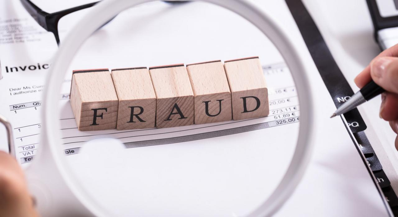 Factura revisada con una lupa, donde se lee la palabra fraude en inglés