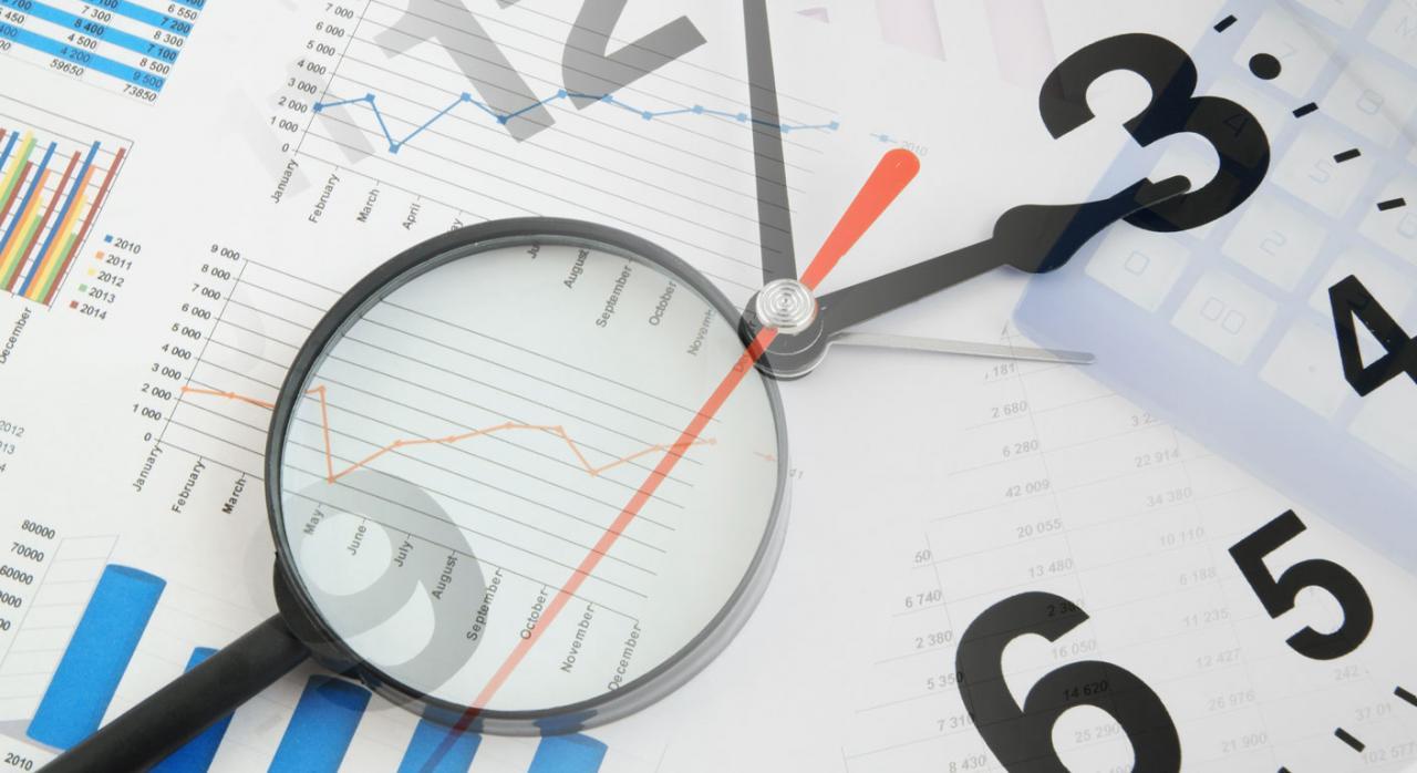 Medidas tributarias en Galicia. Lupa sobre imagen de gráficos financieros y reloj