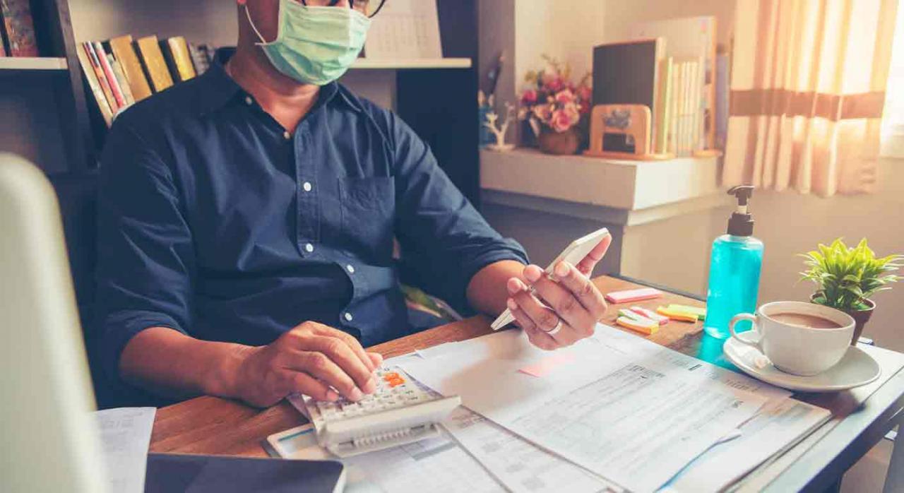 Liquidaciones IVA pandemia. Hombre trabajando usando el móvil y una calculadora con una mesa llena de documentos