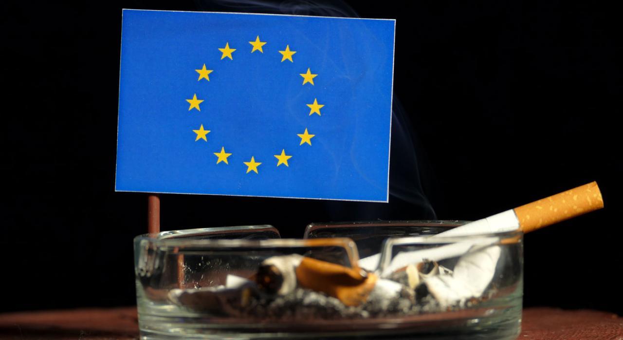 Impuesto especial que grava el tabaco. Cenicero con un cigarrillo y al fondo una bandera de la UE