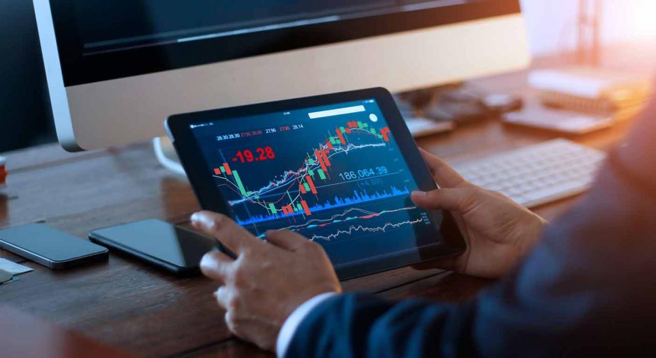Impuesto sobre las transacciones financieras. Hombre revisando gráficas de valores frente a una pantalla de ordenador y una tablet