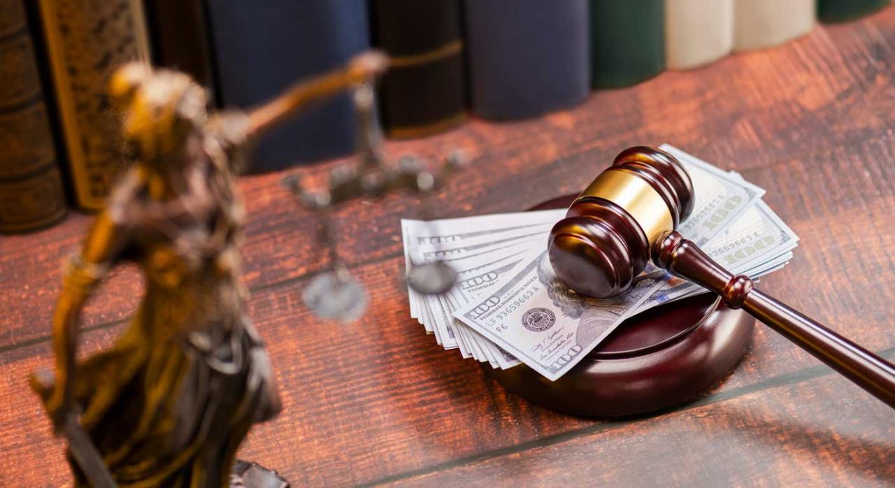 Intereses de demora abonados por la AEAT. Mazo de justicia sobre un montón de billetes
