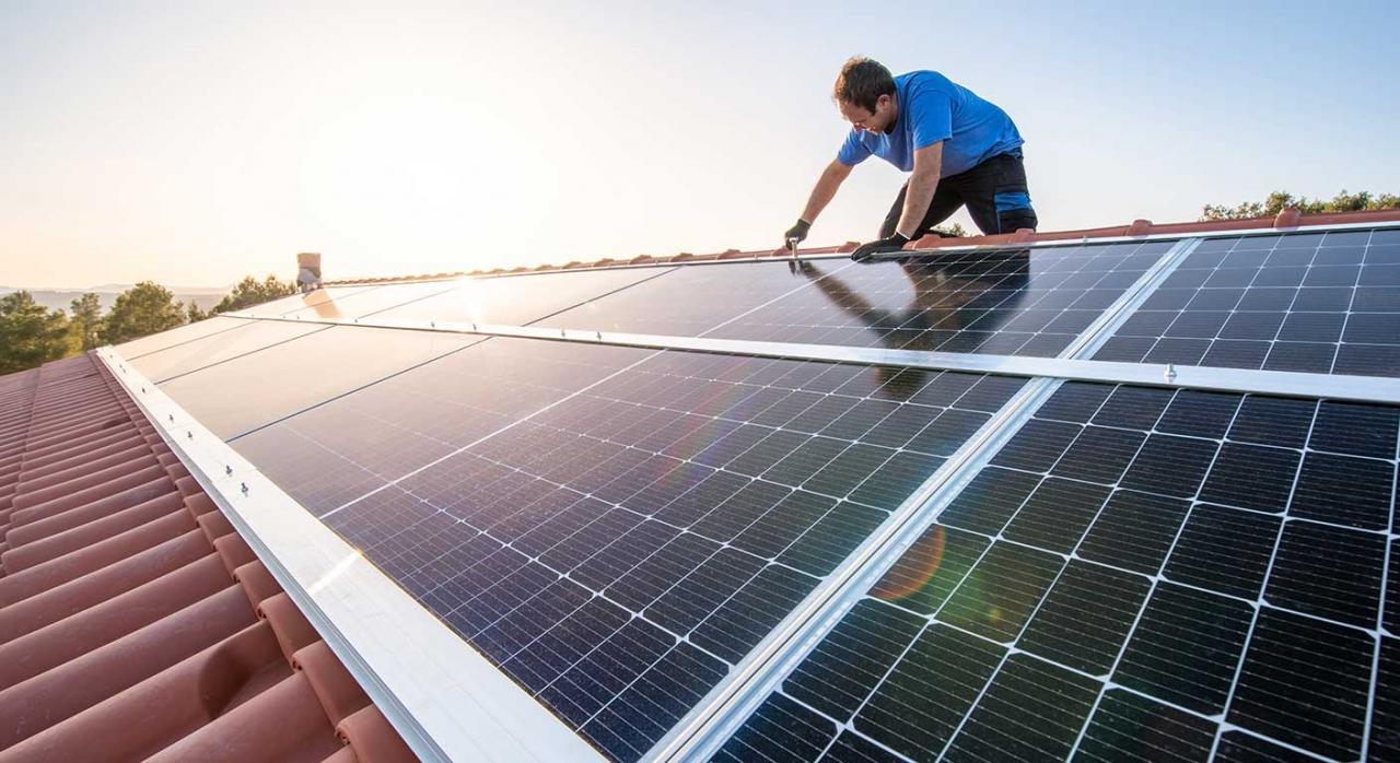 IRPF, deducciones. Imagen de un trabajador profesional instalando paneles solares en el techo de una casa