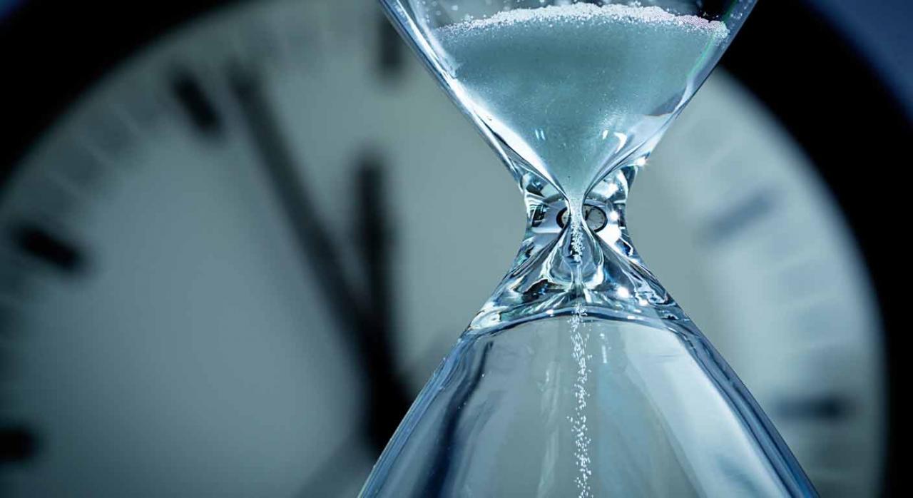 Medidas tributarias en Extremadura. Reloj de arena en primer plano y al fondo reloj analógico