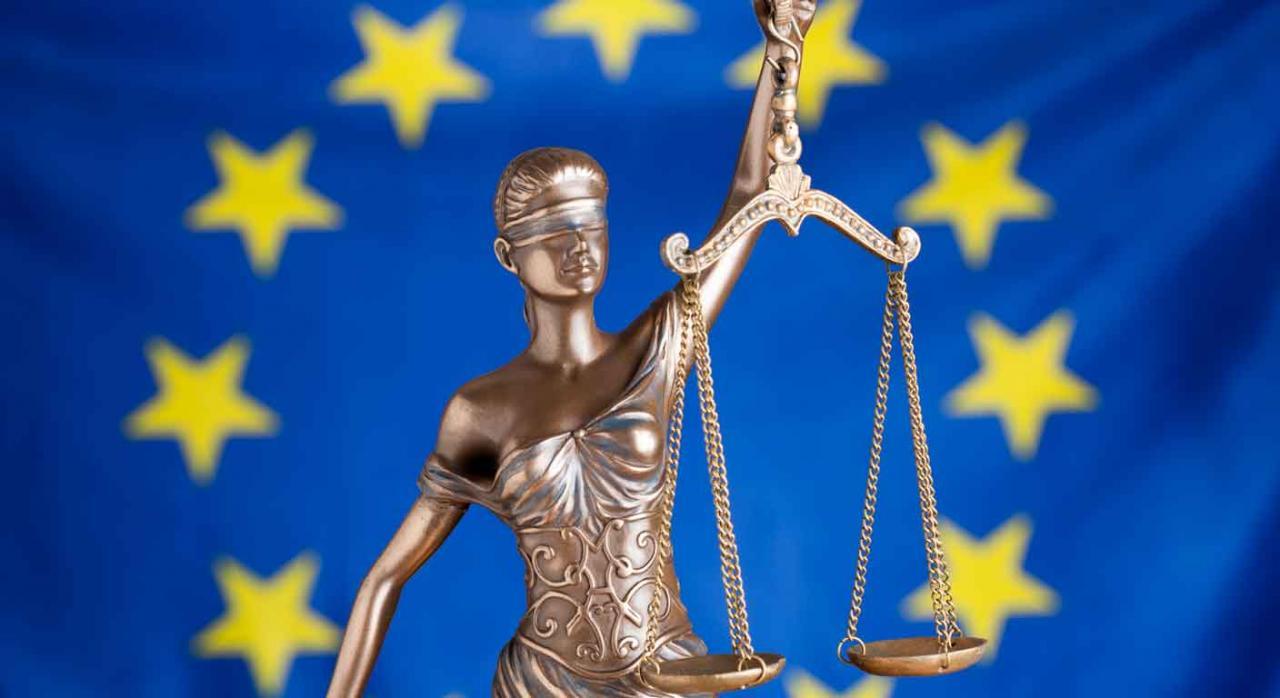 Imagen de la dama de justicia con su balanza y la bandera europea de fonto