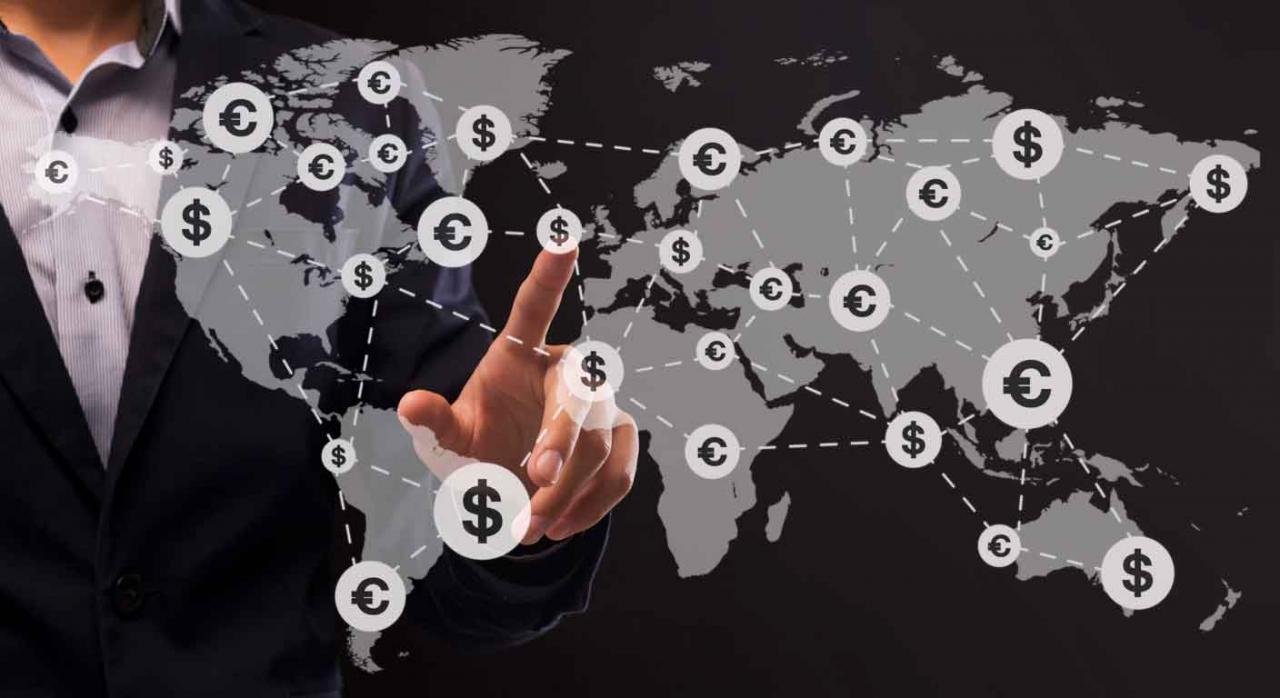Asimetrías fiscales 2016/1164. Empresario señala con el dedo un lugar en el mapa del mundo sobre el que aparecen iconos de divisas