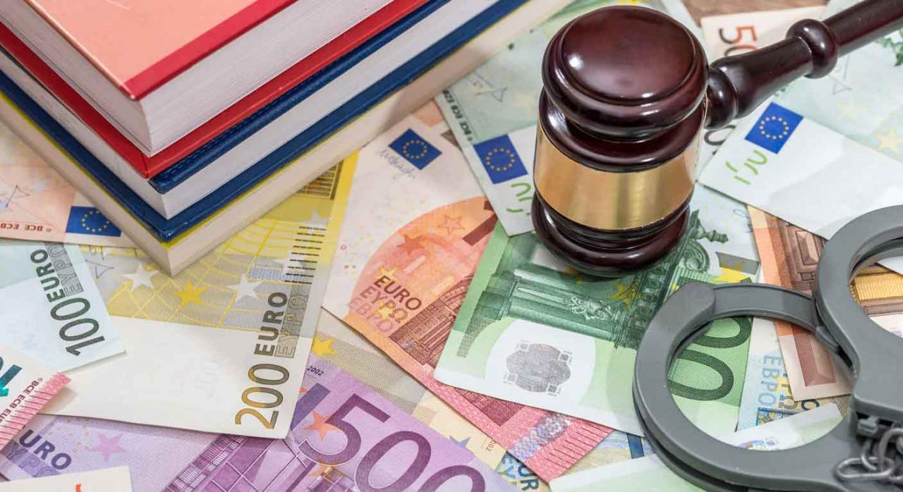 Absolución, delito fiscal, investigación, IVA prescrito. Un mazo de juez, unas esposas y unos libros sobre un montón de billetes