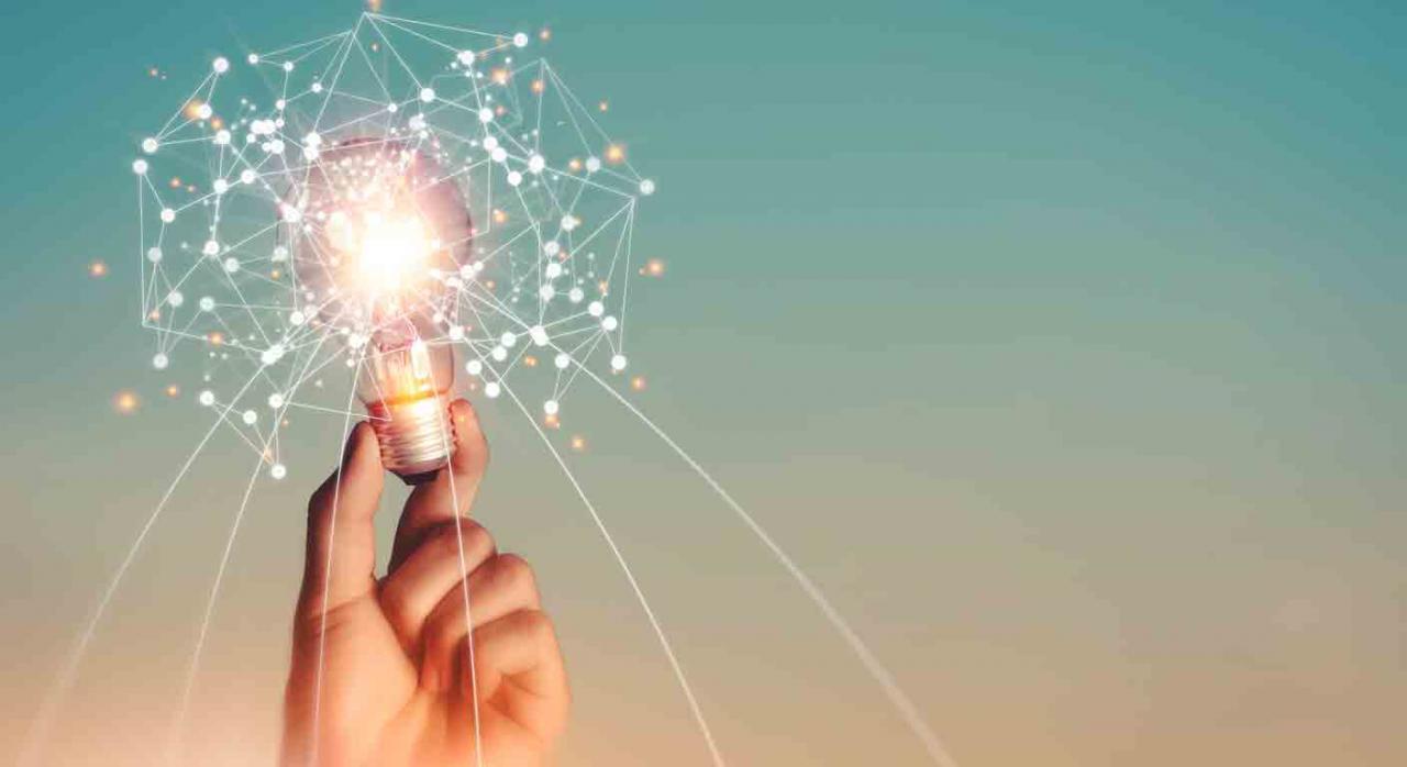 IVA, IVPEE, tipo, reducción, suspensión temporal, energía eléctrica, precio, electricidad. Mano sostiene una bombilla. Concepto de innovación