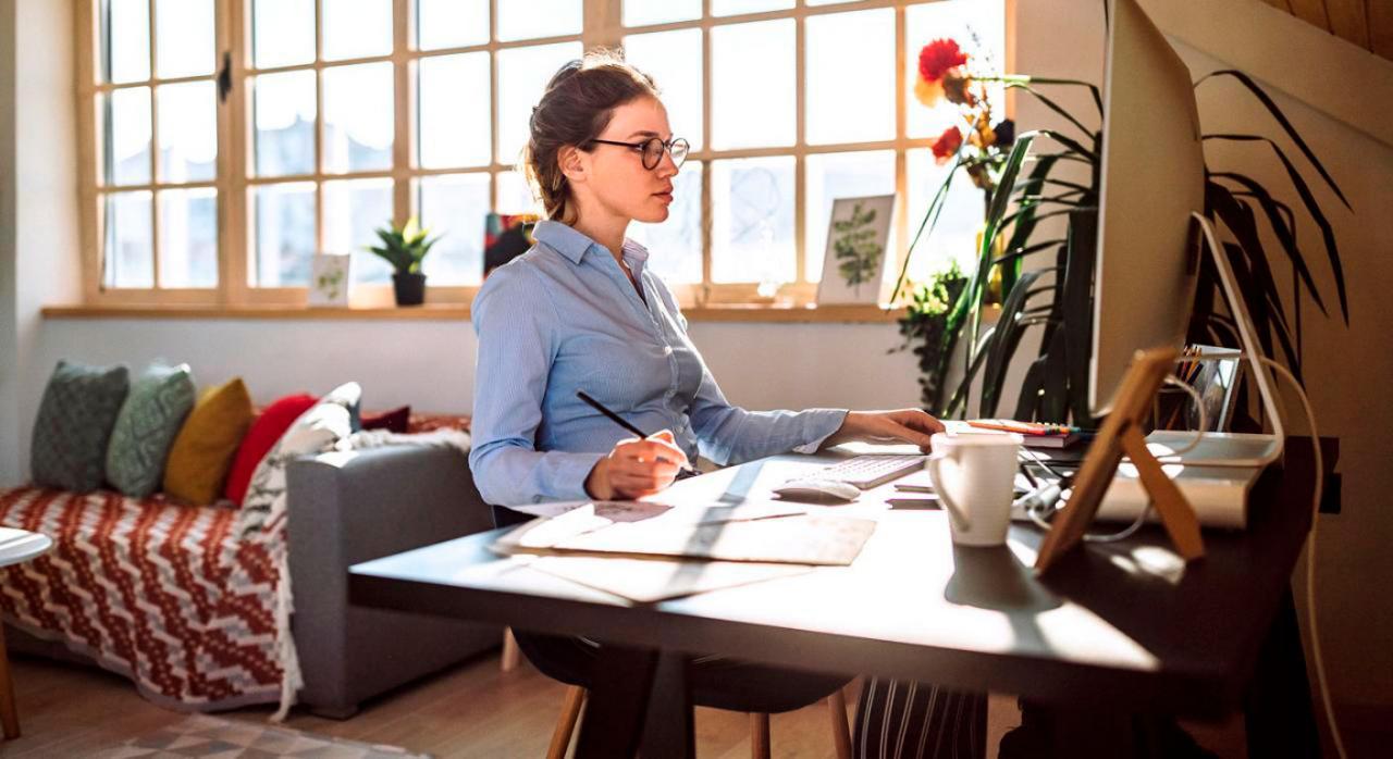 Ley del trabajo a distancia: medidas tributarias. Imagen de una chica teletrabajando desde el salón de su casa