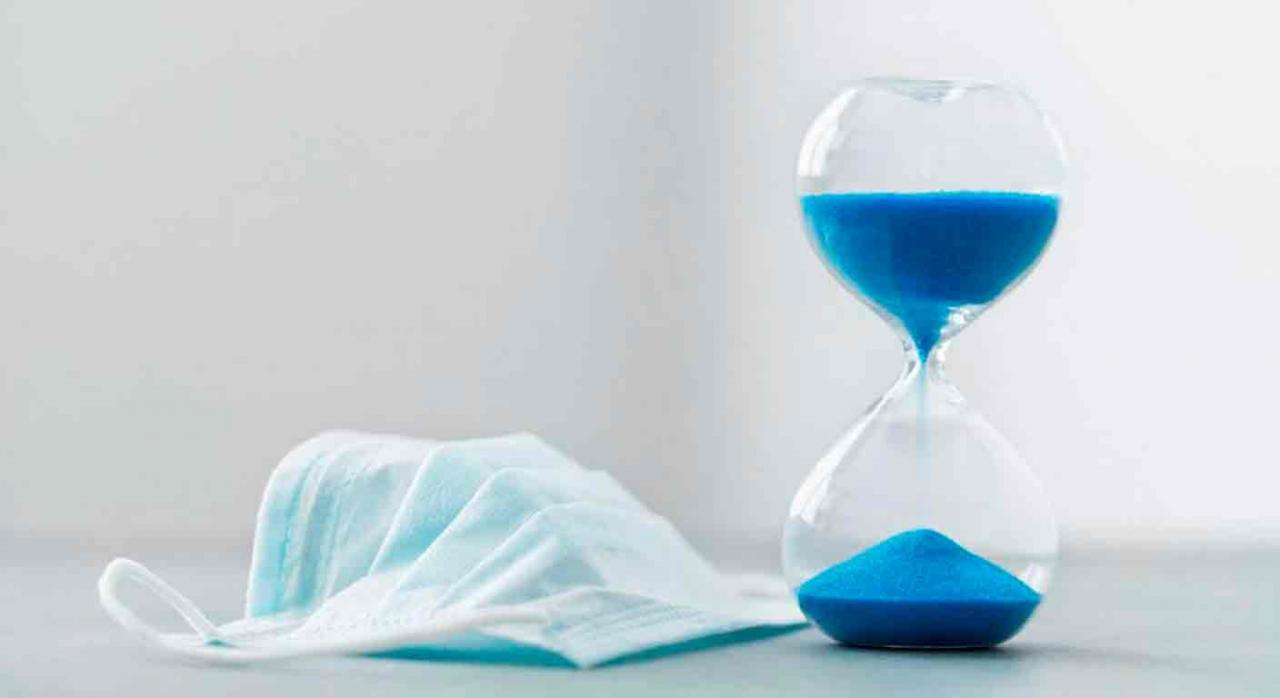 medidas tributarias, COVI-19, Alava, 2021. Un reloj de arena de color azul y una mascarilla al lado