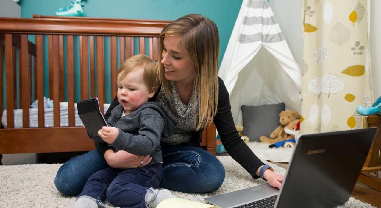 Modelo 140. Mujer sentada en el suelo con un bebe que sostiene una calculadora