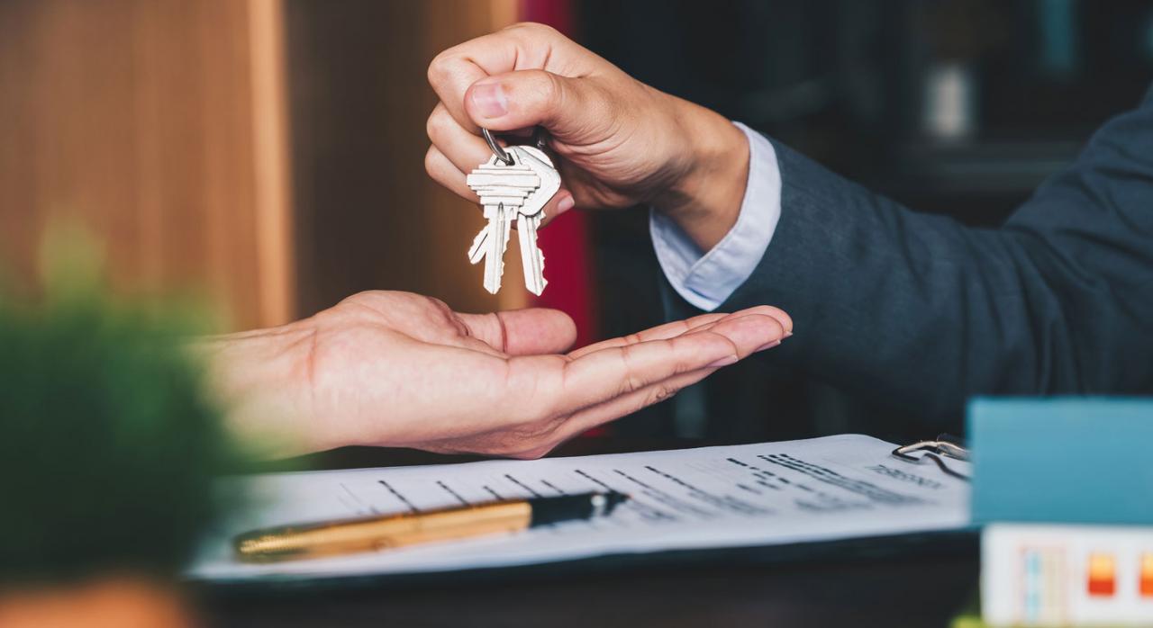 Proyecto de Orden para restablecer la obligación de información de sobre inmuebles turísticos. Imagen de agente inmobiliario entregando llaves de vivienda en mano
