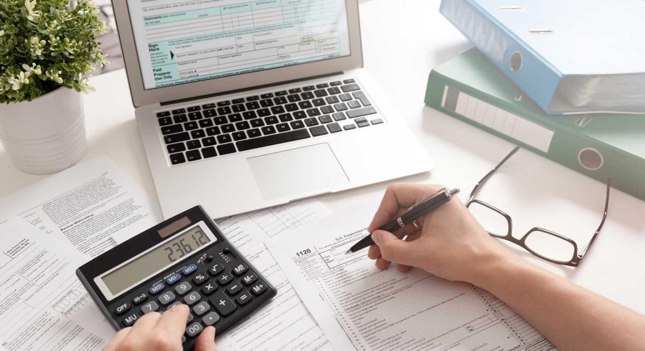 Modelos IRPF e IP 2020. Imagen de Modelos de renta en papel y telemático, una calculadora y un bolígrafo en mano todo en sobremesa