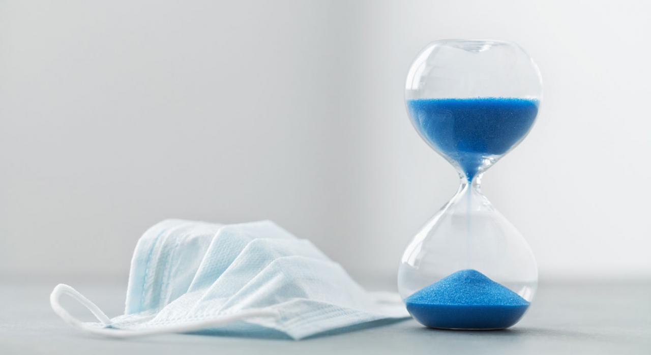 Bizkaia aprueba medidas tributarias adicionales relacionadas con la COVID 19. Imagen de mascarilla quirúrgica y reloj de arena sobre mesa