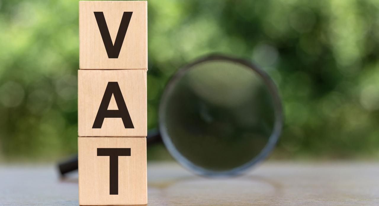 Ley  11/2021: modificaciones en IVA e IGIC. Imagen de cubos de madera superpuestos verticalmente con la palabra VAT escrita y sobre fondo difuminado con lupa