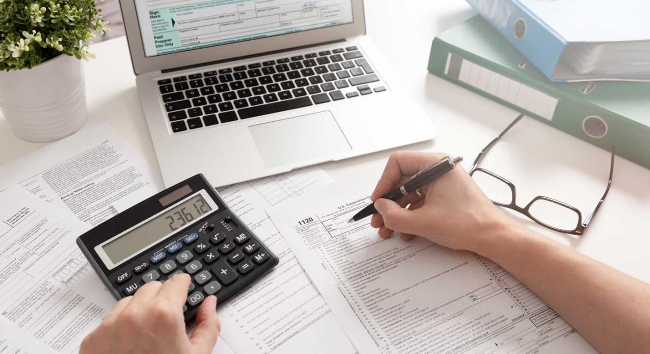 Modificaciones en los modelos de autoliquidación del IVA. Persona frente a portátil y calculadora, rellenando un formulario