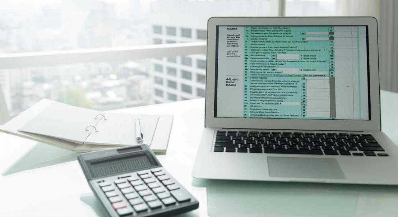 Modificaciones en el Reglamento del IS. Portátil, calculadora y agenda encima de una mesa