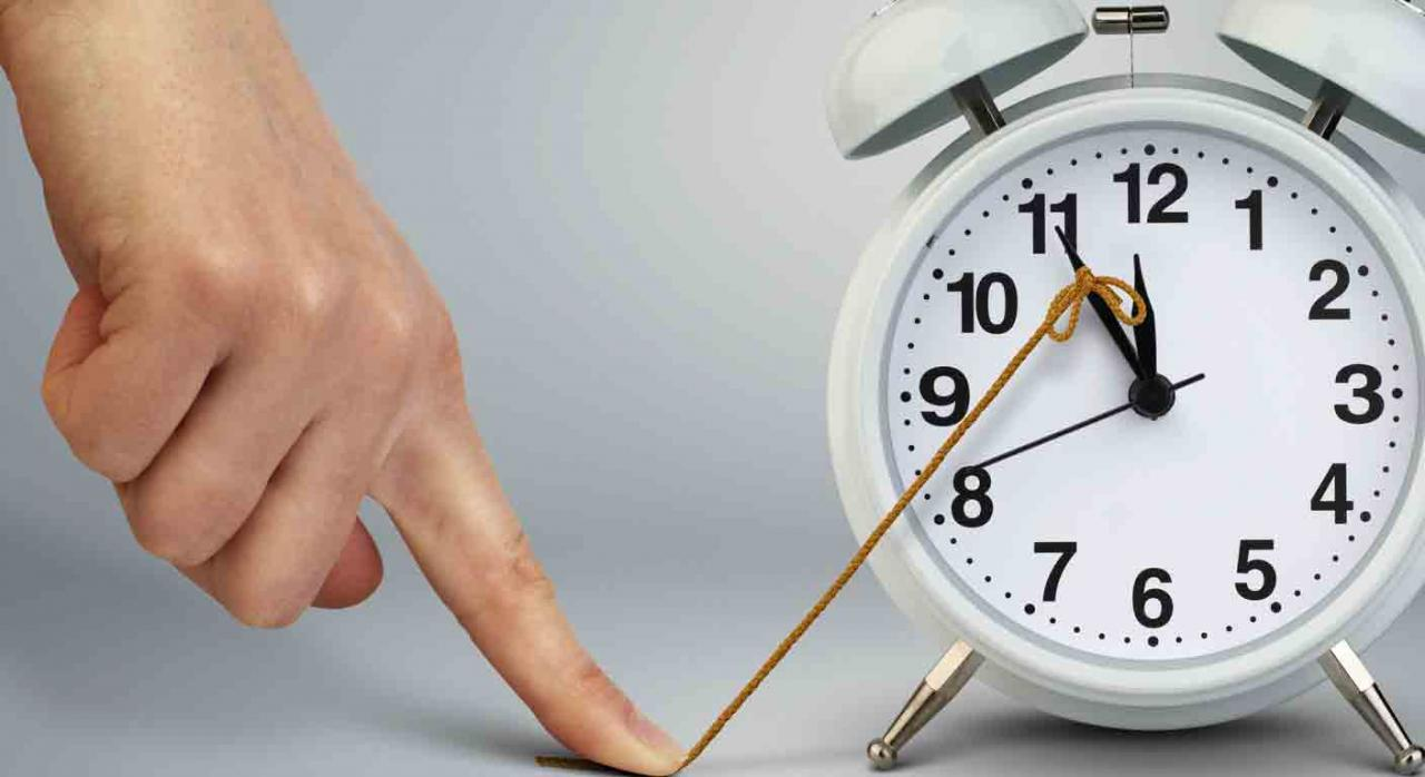 Suspensión actuaciones judiciales. Una mano sujetando una goma con el dedo para parar el avance de las agujas de un reloj despertador